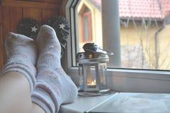 Πόδια στις κάλτσες Χαλάρωση γυναικών στο σπίτι κοντά στο παράθυρο Ντεκόρ στο καθιστικό στοκ εικόνα