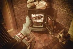 Πόδια στις μάλλινες κάλτσες από την εστία Χριστουγέννων Το άτομο χαλαρώνει από τη θερμή πυρκαγιά με ένα φλυτζάνι του ζεστού ποτού στοκ εικόνα