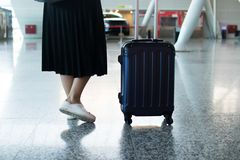 Πόδια ταξιδιωτικών γυναικών που περπατούν φέρνοντας μια βαλίτσα σε έναν αερολιμένα στοκ φωτογραφίες με δικαίωμα ελεύθερης χρήσης