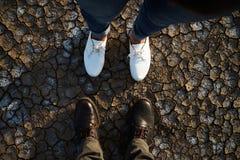 Πόδια του άνδρα και της γυναίκας που στέκονται στο ξηρό χώμα Στοκ Εικόνα