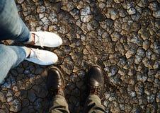 Πόδια του άνδρα και της γυναίκας που στέκονται στο ξηρό χώμα Στοκ Φωτογραφία