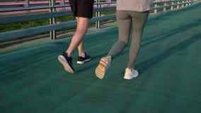 Πόδια του άνδρα και της γυναίκας που τρέχουν στο στάδιο κατά την υπαίθρια, πίσω άποψη απόθεμα βίντεο