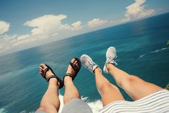 Πόδια του άνδρα στα σανδάλια και της γυναίκας στα αθλητικά παπούτσια που κάθονται επάνω από τον ωκεανό στον απότομο βράχο Στοκ Εικόνες