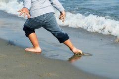Πόδια του αγοριού στα υγρά γκρίζα τζιν που δραπετεύουν από το κύμα στην αμμώδη παραλία Στοκ Εικόνα