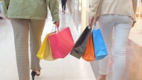 Πόδια του shopaholics με τις τσάντες αγορών που περπατούν κάτω από τη λεωφόρο Σε αργή κίνηση Θηλυκές γυναίκες που περπατούν στη λ απόθεμα βίντεο