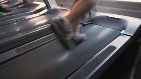 Πόδια του unrecognizable ατόμου που τρέχουν treadmill στο στούντιο ικανότητας Κλείστε επάνω το πίσω χαμηλό πυροβοληθε'ν γωνία ηλι φιλμ μικρού μήκους