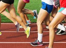 Πόδια των κοριτσιών γυμνασίου που τρέχουν σε μια διαδρομή Στοκ Εικόνες