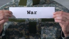 Πόλεμος που γράφεται σε χαρτί στα χέρια του αρσενικού στρατιώτη, της εχθρότητας και της αποσταθεροποίησης απόθεμα βίντεο