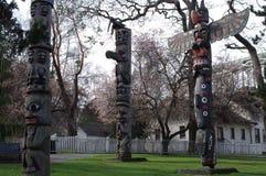 Πόλοι τοτέμ μεταξύ των πρόωρων ανθίζοντας δέντρων άνοιξη στοκ φωτογραφία με δικαίωμα ελεύθερης χρήσης