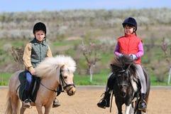 Πόνι οδήγησης αγοριών και κοριτσιών Στοκ εικόνες με δικαίωμα ελεύθερης χρήσης