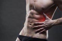 Πόνος στη αριστερή πλευρά αρσενικό σωμάτων μυϊκό Όμορφη τοποθέτηση bodybuilder στο γκρίζο υπόβαθρο Στοκ Εικόνες