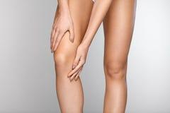 Πόνος σώματος Κινηματογράφηση σε πρώτο πλάνο του όμορφου θηλυκού σώματος με τον πόνο στα γόνατα Στοκ εικόνα με δικαίωμα ελεύθερης χρήσης
