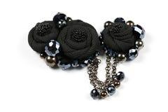 Πόρπη βιοτεχνίας, κρεμαστό κόσμημα υπό μορφή μαύρων λουλουδιών από το ύφασμα και μαύρες εδροτομημένες πολύτιμους λίθους χάντρες,  Στοκ Εικόνα