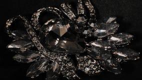 Πόρπη μέσα με τις πέτρες σε μια μαύρη περιστρεφόμενη στάση Κοσμήματα ασφαλίστρου Μακροεντολή φιλμ μικρού μήκους
