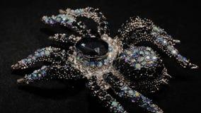 Πόρπη υπό μορφή αράχνης σε μια μαύρη περιστρεφόμενη στάση Κοσμήματα ασφαλίστρου Μακροεντολή απόθεμα βίντεο