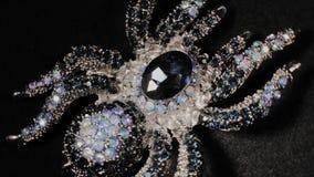 Πόρπη υπό μορφή αράχνης σε μια μαύρη περιστρεφόμενη στάση Κοσμήματα ασφαλίστρου Μακροεντολή φιλμ μικρού μήκους