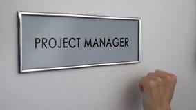 Πόρτα γραφείων διευθυντών προγράμματος, χέρι που χτυπά τη στρατηγική ανάπτυξης επιχείρησης κινηματογραφήσεων σε πρώτο πλάνο στοκ φωτογραφίες με δικαίωμα ελεύθερης χρήσης