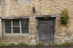 Πόρτα και παράθυρο στο ειδυλλιακό εξοχικό σπίτι, Castle Combe, UK Στοκ Φωτογραφία