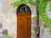 Πόρτα μεταξύ των λουλουδιών και του κισσού Στοκ φωτογραφίες με δικαίωμα ελεύθερης χρήσης