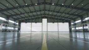 Πόρτα παραθυρόφυλλων κυλίνδρων και τσιμεντένιο πάτωμα μέσα στο κτήριο εργοστασίων για το βιομηχανικό υπόβαθρο Αεροπλάνο μπροστά α απόθεμα βίντεο