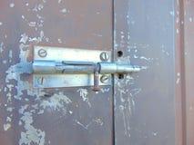 Πόρτα που κλειδώνεται με το μπουλόνι στο παλαιό σκουριασμένο σπίτι κήπων Στοκ Φωτογραφία