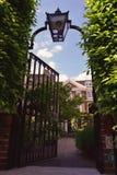 Πόρτα πυλών σιδήρου με το φανάρι που οδηγεί στον ιδιωτικούς κήπο και το σπίτι Στοκ φωτογραφία με δικαίωμα ελεύθερης χρήσης