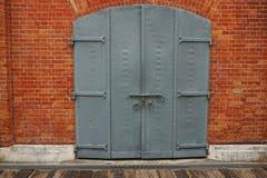 Πόρτα χάλυβα γκρίζα με τα κόκκινα τούβλα Στοκ Εικόνα