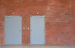Πόρτες μετάλλων στον πορτοκαλή τουβλότοιχο με το διάστημα αντιγράφων στοκ φωτογραφία