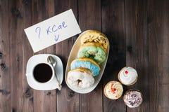 Πόσες θερμίδες στα γλυκά donuts, σημείωση λαβής γυναικών με την ερώτηση στοκ φωτογραφία με δικαίωμα ελεύθερης χρήσης