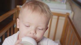 Πόσιμο γάλα αγοριών δύο ετών παιδιών από το πλαστικό μπουκάλι στο κρεβάτι του που ανατρέχει απόθεμα βίντεο