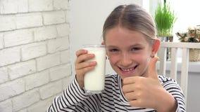 Πόσιμο γάλα παιδιών στο πρόγευμα στην κουζίνα, δοκιμάζοντας γαλακτοκομικά προϊόντα κοριτσιών απόθεμα βίντεο