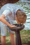 Πόσιμο νερό αγοριών από μια πηγή στοκ φωτογραφίες
