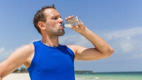 Πόσιμο νερό ατόμων μετά από να τρέξει στην παραλία. Διψασμένος αθλητικός δρομέας Στοκ εικόνες με δικαίωμα ελεύθερης χρήσης