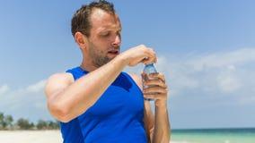 Πόσιμο νερό ατόμων μετά από να τρέξει στην παραλία. Διψασμένος αθλητικός δρομέας Στοκ Εικόνες
