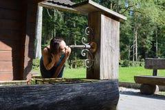 Πόσιμο νερό γυναικών από έναν παλαιό καλά Στοκ φωτογραφία με δικαίωμα ελεύθερης χρήσης