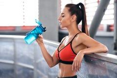 Πόσιμο νερό γυναικών ικανότητας από ένα μπουκάλι Το νέο ενεργό κορίτσι αποσβήνει τη δίψα στοκ φωτογραφία με δικαίωμα ελεύθερης χρήσης