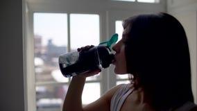 Πόσιμο νερό γυναικών ικανότητας από το μπουκάλι Μυϊκό νέο θηλυκό στη γυμναστική που παίρνει ένα σπάσιμο από το workout φιλμ μικρού μήκους