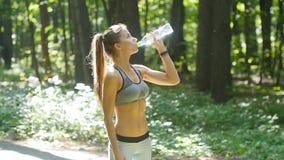 Πόσιμο νερό γυναικών ικανότητας από το μπουκάλι στο ηλιόλουστο δάσος φιλμ μικρού μήκους