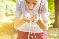 Πόσιμο νερό εφήβων από ένα φρεάτιο στοκ φωτογραφία