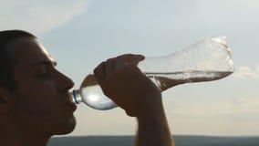 Πόσιμο νερό νεαρών άνδρων από ένα πλαστικό μπουκάλι στη φύση Τύπος που έχει το σπάσιμο νερού στο ηλιοβασίλεμα The Sun στο υπόβαθρ απόθεμα βίντεο