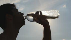 Πόσιμο νερό νεαρών άνδρων από ένα πλαστικό μπουκάλι στη φύση Τύπος που έχει το σπάσιμο νερού στο ηλιοβασίλεμα The Sun στο υπόβαθρ φιλμ μικρού μήκους
