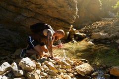 Πόσιμο νερό οδοιπόρων από τον ποταμό Το άτομο απολαμβάνει το καθαρό φρέσκο αμόλυντο νερό στον κολπίσκο βουνών Στοκ Φωτογραφίες