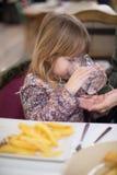 Πόσιμο νερό παιδιών με το πιάτο τηγανιτών πατατών Στοκ εικόνες με δικαίωμα ελεύθερης χρήσης