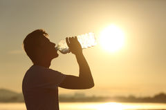 Πόσιμο νερό σκιαγραφιών ατόμων ικανότητας από ένα μπουκάλι Στοκ Φωτογραφίες