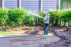 Πότισμα κηπουρών με τη μάνικα νερού στον κήπο στοκ εικόνες