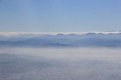 Πόλη και βουνό στην ομίχλη Στοκ Εικόνες