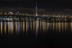 Πόλη του Ώκλαντ και οι αντανακλάσεις λαμπυρίσματος λιμενικών γεφυρών ζωηρόχρωμες στο νερό Στοκ Φωτογραφία
