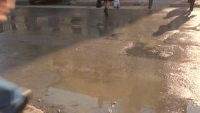 Πόδια ανθρώπων που διασχίζουν την οδό Ηλιόλουστη ημέρα άνοιξη, λακκούβες στο δρόμο απόθεμα βίντεο
