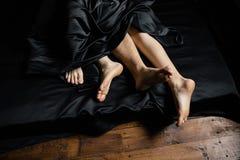 Πόδια ανθρώπων ` s στο κρεβάτι στοκ εικόνες