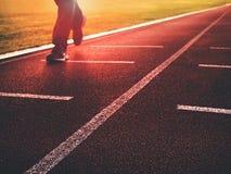 Πόδια ατόμων στο τρέξιμο των παπουτσιών στην κόκκινη πίστα αγώνων στο υπαίθριο στάδιο Στοκ Εικόνες